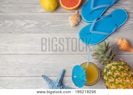 Tropical summer vacation background with pineaplle juice and flip flops on wooden table. View from above. Flat lay