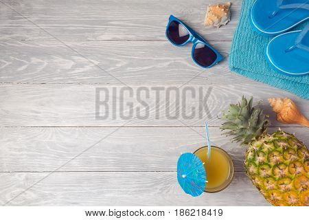 Tropical summer vacation background with pineapple juice and flip flops on wooden table. View from above. Flat lay