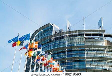 STRASBOURG FRANCE - MAR 31 2017:  The European Parliament building in Strasbourg France with flags waving calmly celebrating peace of the Europe