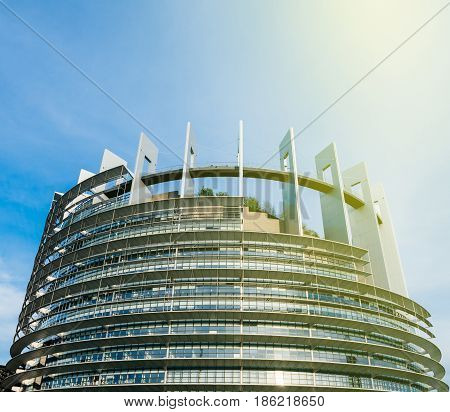 STRASBOURG FRANCE - MAR 31 2017: Wide large view over Official European Union flags - European Parliament building in Strasbourg France with sunbeam sun flare