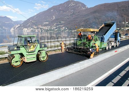 Workers And Vehicles During The Asphalting Of The Highway