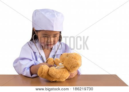 Asian girl playing as a doctor care bear doll isolated background with clipping path.