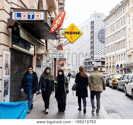 STRASBOURG FRANCE - MAY 7 2017: Three muslims girls walking on trottoir under Loto and press signage in French city of Strasbourg