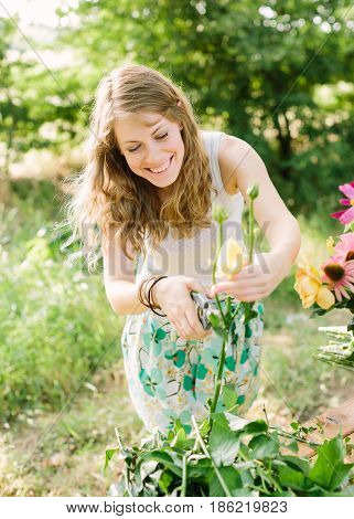 bouquet, people and floral arrangement concept - smiling young beautiful girl in summer garden crops leaves of yellow roses, a hand holding a pruner, eyes closed, pruning shear in female hand