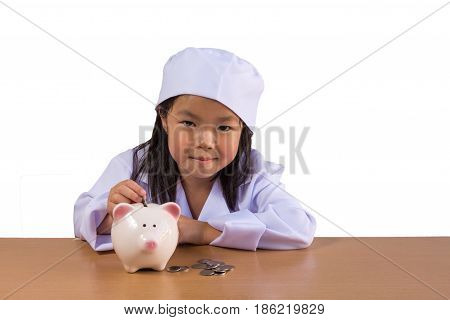 Asian girl playing as a doctor balance money in Piggy Bank isolated background with clipping path.