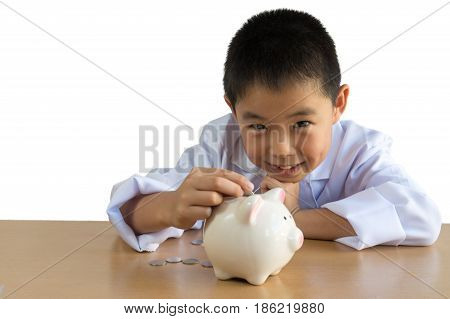 Asian boy playing as a doctor balance money in Piggy Bank isolated background with clipping path.