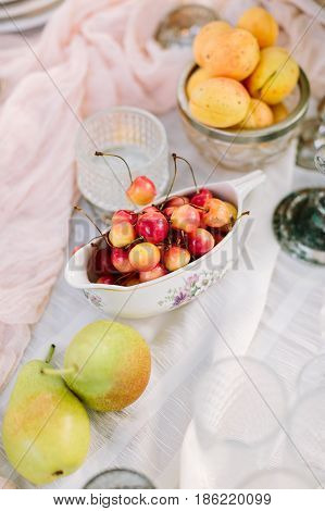 picnic, food, holiday concept - delicious fresh red and yellow cherries, pears, apricots on decorated table for the picnic, fruit plates and dishes, vegan food, white tablecloth, clean and fresh fruit
