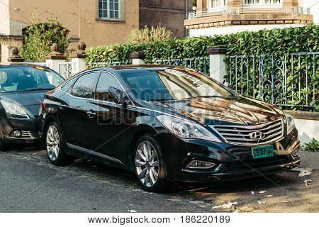 STRASBOURG FRANCE - MAR 3 2017: Front view of Luxury black Hyunday Azera or Hyundai Grandeur parked on a city street under magnolia tree in bloom