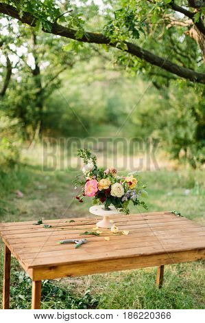flower, summer and floral arrangement concept - desk florist on the summer glade among trees, beautiful fresh bouquet of white and yellow roses, peonies, red carnations, in white vase on wooden table