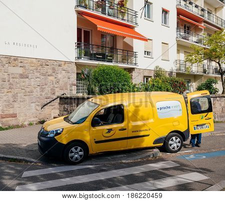 STRASBOURG FRANCE - APR 12 2017: Yellow van of La Poste - French National Postal service with postal driver worker searching gor the right parcel to deliver near French building