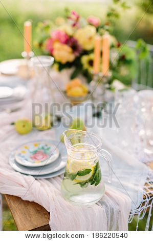 picnic, food, summer, holiday concept - full glass jug of fresh lemonade on festive table, slices of lemon, lime, mint leaves in flagon, bouquet, candles, glasses and plates, fruits, selective focus