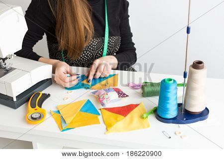 needlework and quilting in the workshop of a young tailor woman - close-up on tailor hands with pieces of colored cloth on the table with threads, fabrics, needles and sewing machine
