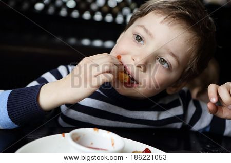 Child eating chicken nugget in a restaurant