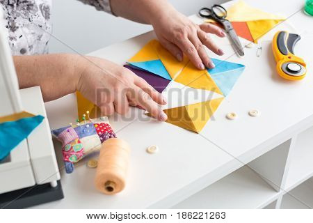 needlework hand quilting in the workshop of a tailor woman on white background - the hands of tailor collect from the desktop scraps of colored fabric for patchwork on the sewing machine