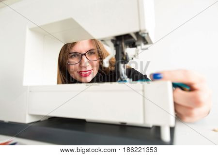 needlework and quilting in the workshop of a tailor - beautiful smiling woman with glasses at work on sewing machine