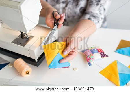 patchwork and quilting in the workshop of a tailor woman on white background - close-up on hands of a tailor woman at work with scissors and colorful stitched in fabric