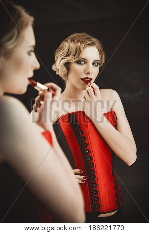 The beautiful young woman stands in front of a mirror and paints her lips. Retro (vintage) style