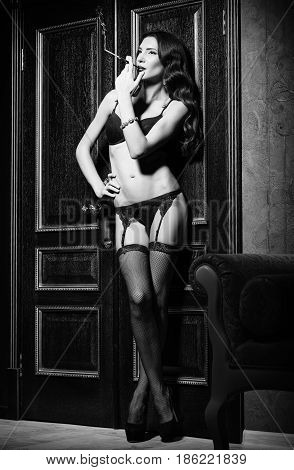 Film noir style: dangerous sexy young woman in lingerie standing at the door and smoking cigarette. Black and white
