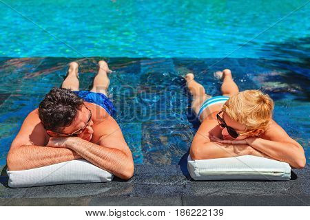 Successful retirement recreation summer vacation concept. Retired mature couple enjoying beautiful sunny day in swimming pool at beach club. Happy senior woman and man lying in water at poolside.