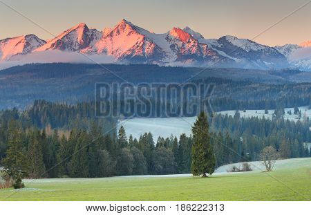 Snowy Mountainpeaks In Red Sunligh