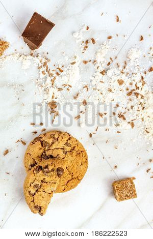 The process of making chocolate chips cookies. Overhead shot of biscuits with chocolate shavings, flour, and cane sugar around them, with a place for text