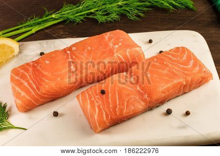 Two slices of salmon on a dark background with a place for text, with peppercorns, and dill sprig