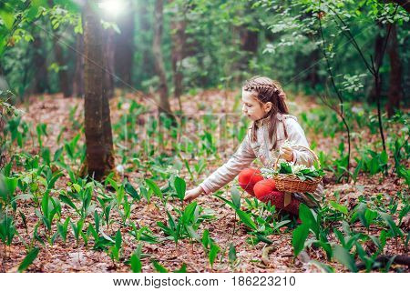 Little cute blonde girl picking bouquet of Lily of the valley in the woods on a sunny day