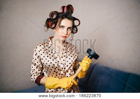 A woman with curls on her head in a lace dressing gown is keeping a cleaning agent in the pipes. The concept of cleaning garbage without plumbing.