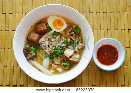 Chinese rice flour paste with pork and entrails topping creamy egg yolk in soup
