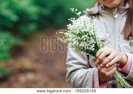 girl holding a bouquet of lilies of the valley