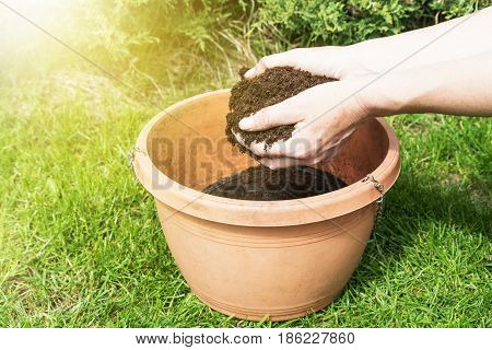 Female hands are putting soil into a flower pot outdoors. Photo is edited by sun lights in the upper left corner.