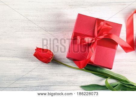 Beautiful tulip and giftbox on light wooden background