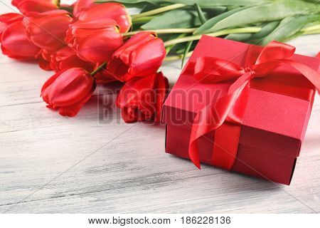 Bouquet of beautiful tulips and giftbox on light wooden background, closeup