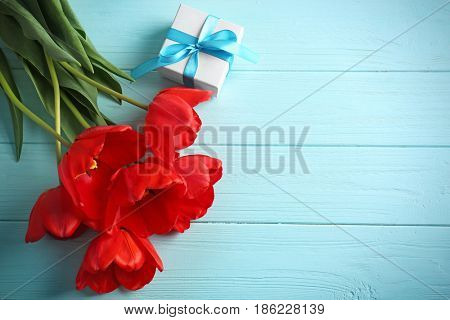 Beautiful tulips and giftbox on wooden background
