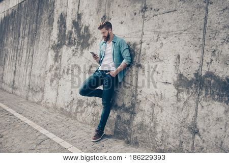 Hot Young Stylish Guy Is Standing Near The Concrete Wall Outside And Browsing On His Pda. He Has A F