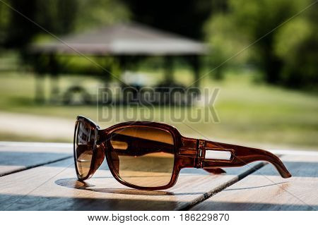 Sunglasses On The Table In The Sun On A Wooden Table