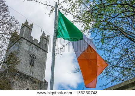 Irish flag fluttering in front of the tower of an Old St Mary Cathedral, Limerick, Ireland