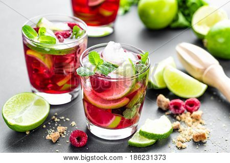 Raspberry mojito cocktail with lime mint and ice cold iced refreshing drink or beverage