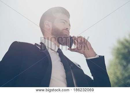 Low Angle View Of A Young Fashionable Bearded Business Man In A Classy Suit Talking On The Phone On