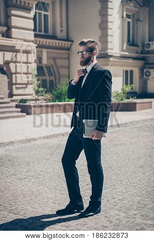 Full Size Photo Of An Intelligent Stylish Bearded Man In A Suit And Glasses Outdoors. He Is Holding
