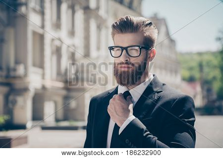 Close Up Portrait Of A Successful Young Red Bearded Guy In Suit And Glasses, Fixing His Tie. So Styl