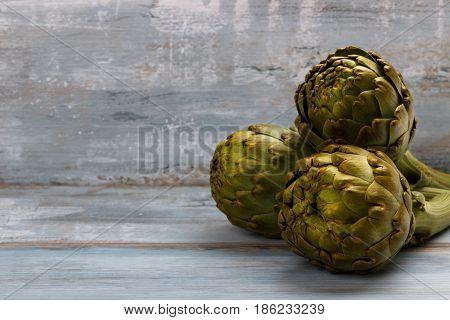 Ripe organic artichokes on rustic wooden board,