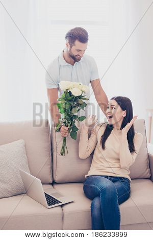 Surprised Young Woman Receiving Flowers From Her Husband. It`s Unexpected, She Is Very Happy