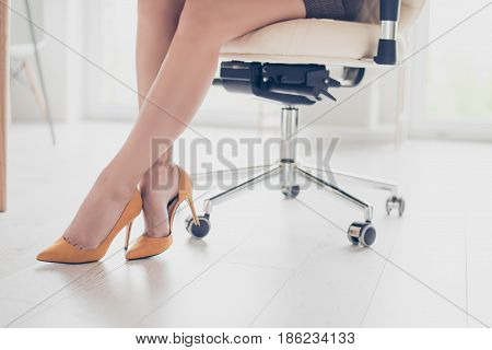 Close Up Cropped Photo Of Beautiful Legs Of The Business Lady In High Hills Shoes. She Is Sitting In