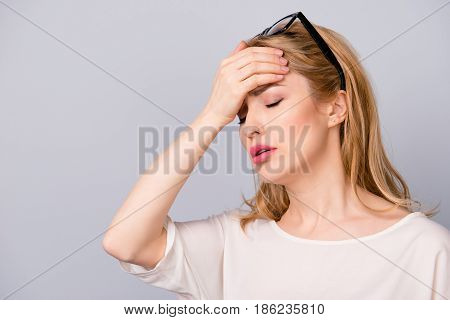 Sad Woman With Blonde Hair Touching Her Forehead Because Of Having Terrible Headache