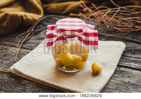 compote of grapes in a jar standing on a wooden table