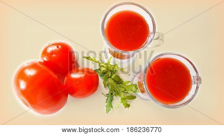 Still life on a white table with tomatoes, arugula  and two glasses of tomato juice.