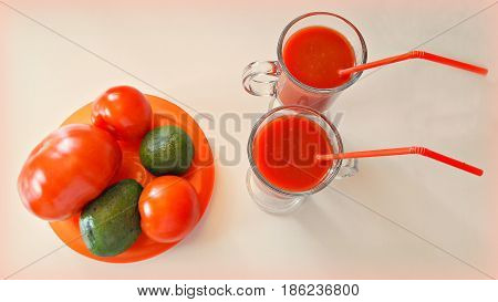 Still life on a white table with tomatoes, avocado, and tomato juice in two glasses with straws.