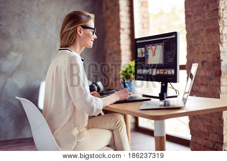 Portrait Of Young Satisfied Smiling Woman Sitting At The Table At Home And Working With Photos