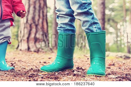 Children standing in wellies in the forest in summer